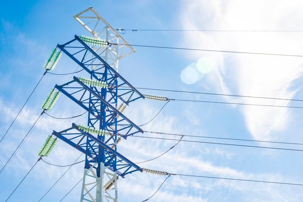 a-high-voltage-electricity-pylons-against-blue-sky-and-clouds-power-line-electric-post.jpg