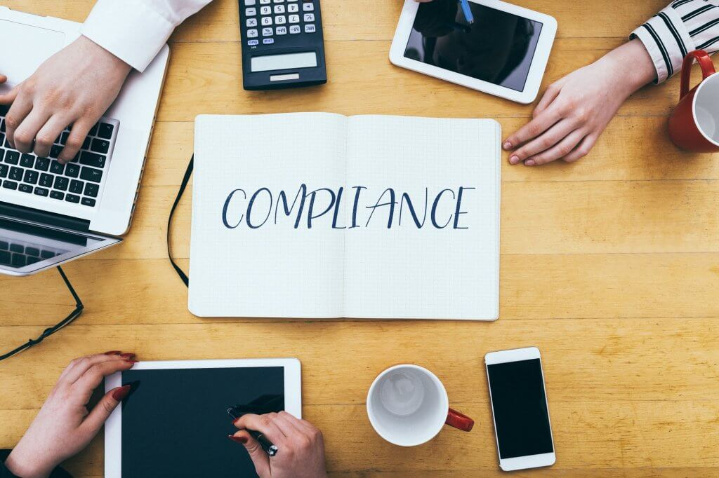 compliance-headline-on-paper-notebook-at-small-business-office-desk-with-young-adult-workers-1.jpg