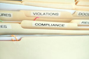 Compliance in the workplace. Folders labeled Compliance, Violations in focus.