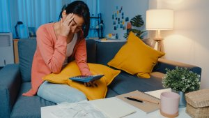 Asian lady feel stress and worried with bill and invoice credit card on sofa at home.